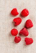 Many red ripe raspberry fruit, on gray linen table cloth with copy space design ready