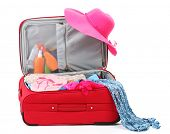 Suitcase with summer clothes, a hat and suntan isolated on white
