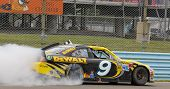 WATKINS GLEN, NY - AUG 12, 2012:  Marcos Ambrose (9) holds off a hard charging field to win the Fing