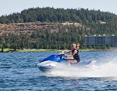 pic of waverunner  - Beautiful woman out on the lake riding a wave runner on bright sunny day - JPG