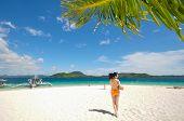 one bikini girl holds coconut on white beach