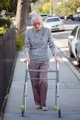 stock photo of street-walker  - Senior woman walking with walker on street - JPG