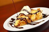 A picture of home-made apple pie served with vanilla ice-cream and chocolate sauce