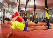 Crossfit fitness TRX training exercises at gym woman and man side push-up workout