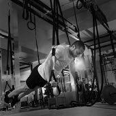 stock photo of pull up  - Crossfit fitness TRX push ups man workout at gym - JPG