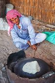 HURGHADA, EGYPT - APR 16, 2013: Unidentified people baking bread in the bedouin village on the deser