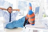Designer relaxing at desk with no shoes and smiling in bright modern office