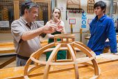 Teacher explaining a structure to two students while standing in a woodwork class