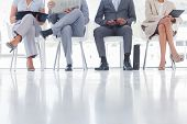 stock photo of crossed legs  - Group of well dressed business people waiting in waiting room - JPG