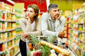 stock photo of supermarket  - Image of young couple with cart in supermarket - JPG
