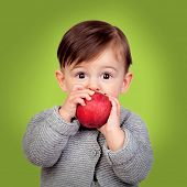 Adorable baby eating a red apple on a green background