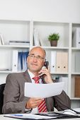 Businessman Holding Document While Using Landline Phone