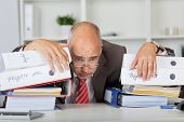 Overworked Businessman Leaning On Stack Of Binders