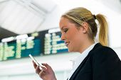 business woman writes on sms airport. roaming charges when abroad. accessibility with modern technol