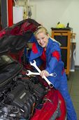 a young woman as a mechanic in a garage. rare professions for women. car is being repaired in the wo