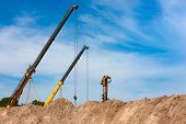 foto of auger  - Two construction cranes and one auger working at construction site peeking out from behind mounds of dirt with blue sky in background - JPG