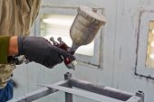 Male hand in glove with spray paint gun, painting car details
