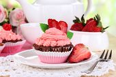 Beautiful strawberry cupcakes on dining table close-up