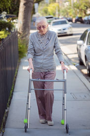 stock photo of street-walker  - Senior woman walking with walker on street - JPG
