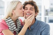 Happy casual young woman kissing man on his cheek