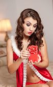 Young sexy Santa holding a gift, boudoir shoot. Attractive brunette with long hair wearing lingerie