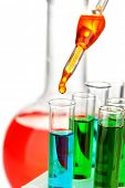 stock photo of reagent  - Laboratory pipette with drop of color liquid over glass test tubes - JPG