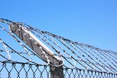 Coiled Razor Wire Fence Against Blue Skyline