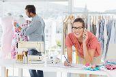 Male and female fashion designers at work in a bright studio