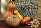 Pumpkins with apples and sheaf on wooden board on sackcloth background