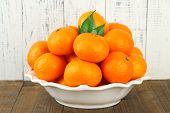 Ripe tangerines in bowl on table on wooden background