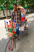 DHAKA, BANGLADESH - SEPTEMBER 17, 2009: A traditionally ornamented cycle rickshaw and driver. Richsh