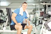 Smiling man seated on a bench drinking water after exercise in fitness gym, with very shallow DOF