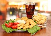 Fried chicken nuggets with vegetables,cola,french fries and sauce isolated on white