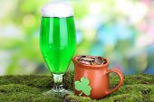 Glass of green beer and pitcher with coins on grass on natural background