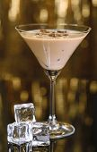 stock photo of bailey  - Baileys liqueur in glass on golden background - JPG