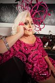 pic of drag-queen  - Blond drag queen in pink dress sitting on sofa - JPG