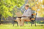 Senior man with hat sitting on a wooden bench and working on a laptop in a park