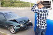 Stressed Driver Looking The Car After Traffic Accident