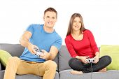 Young couple sitting on a modern sofa and playing video game isolated on white background