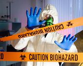 Scientist behind caution tape in hazardous biochemicals laboratory.