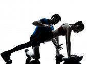 personal trainer man coach and woman exercising abdominals push ups on bosu silhouette studio isolat