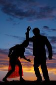 image of bent over  - A silhouette of a woman bent over with her man - JPG