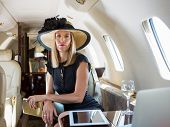 Portrait of confident rich woman sitting in private jet