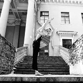 Attractive teen girl dancing outdoor in park against old building with columns. Black and white.