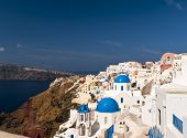 stock photo of cupola  - Santorini houses and blue cupola churches on the volcanic rock - JPG
