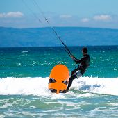 young sportsman kite sergfer on clean beach on a background of mountains  in summer day