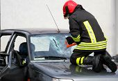 Fireman With Work Gloves While Breaking A Car Windshield To Release The People Injured After Car Acc