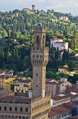 Bird eye view on a tower of Vecchio palace in Florence with surrounding Tuscany hills in a backgroun