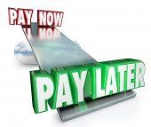Pay Now Vs Later words on a see saw or balance borrow money or apply for credit