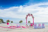 wedding arch decorated with flowers on tropical sand beach, outdoor beach wedding setup